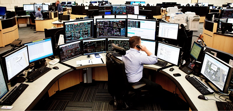 Person at desk with multiple monitors
